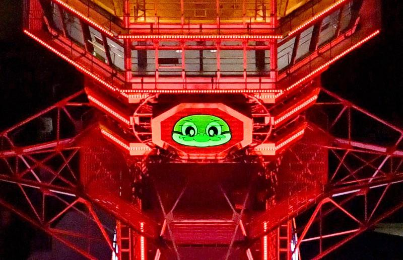 大阪府の独自基準「大阪モデル」が「赤信号」となり、赤色にライトアップされた通天閣で、涙目になった府公式マスコットの「もずやん」=大阪市浪速区で2020年12月3日午後8時15分、本社ヘリから山田尚弘撮影