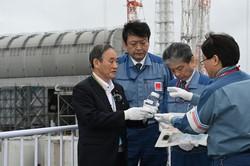 2050年までの脱炭素化を打ち出した(東京電力福島第1原発で汚染処理水の入った瓶を手に、浄化の仕組みなどについて説明を受ける菅義偉首相)