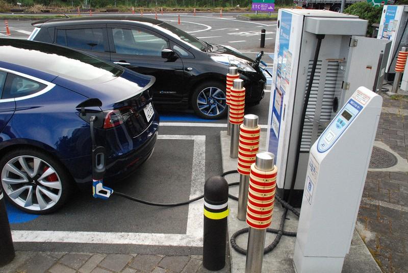 揮発油税を奪うEV(初代日産リーフと並び急速充電するテスラモデル3)