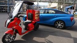 トヨタ自動車の燃料電池車「ミライ」から充電する日本マクドナルドの配達用電動バイク(手前)
