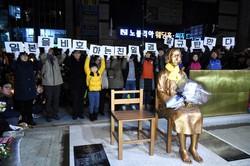 釜山の日本総領事館前に設置された少女像の除幕式。周辺は市民団体やメディア、警察でもみ合いとなった。プラカードのハングルは「日本をかばう親日警察を糾弾する」と書かれている=釜山市で2016年12月31日、大貫智子撮影