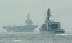 米海軍の空母キティホーク(左)の隊列の最後尾につき東京湾を出る護衛艦=2001年9月21日午後8時半、須賀川理撮影