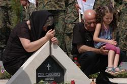ロシアとの戦闘で近親者を亡くし、墓前で悲しむ人々=トビリシで2009年8月、大前仁撮影