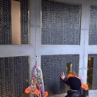 「慰霊と復興のモニュメント」地下に掲示している亡くなった人の銘板をなぞる女性=神戸市中央区で2020年1月17日午前9時53分、平川義之撮影
