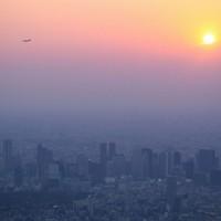 「緊急事態宣言」発令から間もなく1日が経つ夕方、夕日に染まる新宿の高層ビル群。中央は東京都庁=東京都新宿区で2020年4月8日午後5時51分、本社ヘリから吉田航太撮影