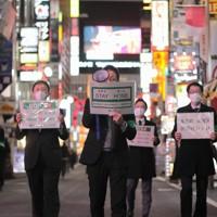 新型コロナウイルスの感染拡大が続く中、新宿・歌舞伎町の繁華街で帰宅を呼びかける東京都の職員=東京都新宿区で2020年4月11日午後6時33分、喜屋武真之介撮影