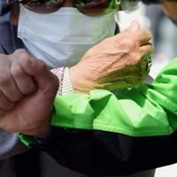 新型コロナウイルスの感染が広がる中、告示日に握手の代わりに有権者と腕で触れあう衆院静岡4区補選の候補者(右)=静岡市清水区で2020年4月14日午前10時5分、滝川大貴撮影