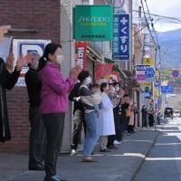 正午になり、店舗の前に並んで一斉に「フライデー・オベーション」の拍手を送る人たち=静岡県裾野市の「すその駅前中央商店街」で2020年4月24日午後0時2分、手塚耕一郎撮影