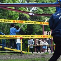 25日から来月6日まで都立公園の駐車場や広場などが閉鎖されるのを前に、「立入禁止」と書かれたテープを張る公園の職員。小学2年の子供を遊ばせていた会社員の女性(38)は「遊具も禁止されてしまうと、ゴールデンウイークをどうやって過ごせばいいのか不安」と話していた=東京都練馬区の都立光が丘公園で2020年4月24日午後3時50分、滝川大貴撮影