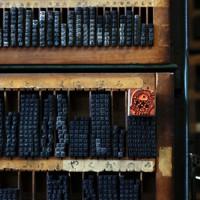 活版印刷に使われる年代物の活字の中に「アマビエ」がデザインされたゴム印を置く。オレンジ色に浮かぶ妖怪の姿がひときわ目立った=札幌市西区の日章堂印房で2020年4月24日、貝塚太一撮影