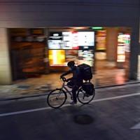 外出自粛が呼びかけられる都内で、飲食店から注文客の家まで料理を運ぶ配達員の男性。新型コロナウイルスの影響でデリバリーサービスの需要が高まっており、この男性も多い日で1日20数件を請け負うという=東京都豊島区で2020年4月29日午後6時38分、北山夏帆撮影