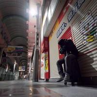 仕事も住む場所も失い、ミナミの商店街で深夜に座り込んでいた男性=大阪市中央区で2020年4月、平川義之撮影