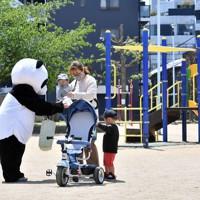 外出自粛で満足に外に出られない親子に少しでも喜んでもらいたいとパンダの着ぐるみを着て弁当を宅配するカフェ「ラフラフラフ」のオーナー=大阪市西成区で2020年4月30日、平川義之撮影