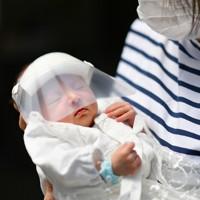新型コロナウイルスから新生児を守るために作られたフェースシールドをつけた赤ちゃん(左)を抱く女性=大阪府八尾市で2020年5月13日、山田尚弘撮影