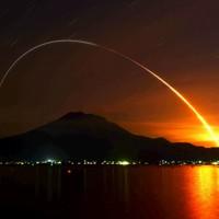 桜島の上空で弧を描く無人補給機「こうのとり」9号機を載せたH2Bロケットの光跡(7分間露光)=鹿児島市で2020年5月21日午前2時半、須賀川理撮影