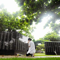 親類の氏名が刻まれた平和の礎に手を合わせる女性=沖縄県糸満市の平和祈念公園で2020年6月23日午前6時、津村豊和撮影
