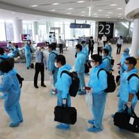 防護服を着てベトナム行きの臨時便に搭乗する乗客=成田空港で2020年6月25日午前10時59分、長谷川直亮撮影