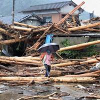 激しい雨が降る中、道路をふさぐ流木に気を配りながら自宅へと戻る男性。冠水していた道路の水が引いたので車を取りにきたという=熊本県球磨村で2020年7月7日午前8時29分、幾島健太郎撮影