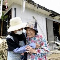 水害で変わり果てた自宅に戻り、親戚の女性と抱き合いながら、涙ぐむ椎屋シヅヨさん(86・右)。「情けないやら、悲しいやらなんともいえ合い。もうなるようにしかならない。命があっただけでもありがたいと思わないと」と話した。この日は、親戚が集まり自宅の片付けなど復旧作業を手伝ってもらっていた=熊本県球磨村で2020年7月8日午前10時50分、望月亮一撮影