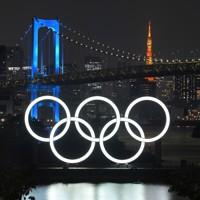 東京・台場の海辺を照らす五輪マークのモニュメント。奥は医療従事者を応援するため青色にライトアップされたレインボーブリッジ=東京都港区で2020年7月20日、手塚耕一郎撮影
