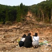 3人が亡くなった土砂崩れ現場で花を手向け手を合わせる人たち=熊本県芦北町で2020年8月4日午後5時54分、徳野仁子撮影