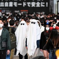 ハロウィーンの外出自粛を呼びかける看板が掲げられる中、大勢の人が行き交うスクランブル交差点をおばけの仮装で歩く人たち=東京都渋谷区で2020年10月31日午後7時12分、北山夏帆撮影