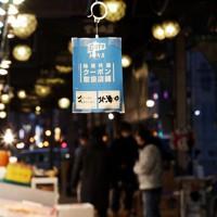 さっぽろ二条市場に吊された「GOTOトラベル地域共通クーポン」が使える案内。三連休最終日の本日午後からは人出が一気に減ったと店の人は話した=札幌市中央区で2020年11月23日午後4時18分、貝塚太一撮影