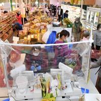 ビニールのカーテンの中でレジ打ちをするスーパーの店員ら=東京都練馬区で2020年4月24日、大西岳彦撮影