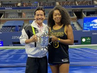 Tennis player Naomi Osaka, right, holds the trophy with her trainer Yutaka Nakamura after winning the U.S. Open tennis championships in this photo provided by Nakamura in New York in September, 2020.
