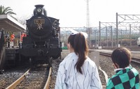 """Two children dressed up as characters from the popular manga and anime series """"Demon Slayer: Kimetsu no Yaiba"""" are seen gazing at a train like the one in the series' film adaptation, at the Kyoto Railway Museum in Shimogyo Ward, Kyoto, on Dec. 26, 2020. (Mainichi/Kenji Yagura)"""
