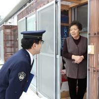 仮設住宅に住むお年寄りを訪問し声をかける警察官=福島県二本松市で2012年1月11日午前10時30分、武市公孝撮影