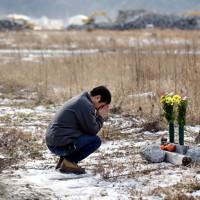 東日本大震災から1年10カ月となった月命日の11日、自宅跡地に献花し手を合わせる男性=陸前高田市で、2013年1月11日午前11時37分、小川昌宏撮影