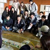 タイムカプセルの中身に笑顔を見せる新成人たち=岩手県山田町の大沢小体育館で2019年1月12日午後、篠口純子撮影