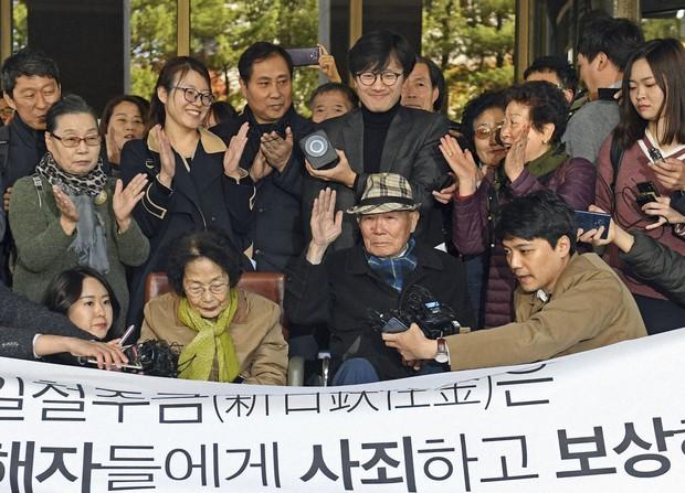 韓国の元徴用工訴訟で日本企業に賠償を命じた判決が確定し、支援者らから拍手を送られる原告の李春植さん(手前右から2人目)=2018年10月、韓国最高裁前(共同)