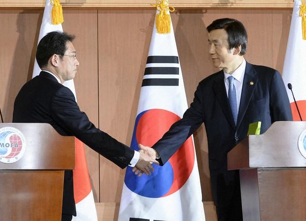 「慰安婦合意」の共同記者発表を終え、握手する岸田外相(左)と韓国の尹炳世外相=2015年12月28日、ソウルの韓国外務省(共同)
