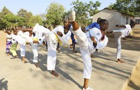 Natsiraishe Maritsa, second right, goes through taekwondo kicking drills during a practice session with young boys and girls in the Epworth settlement about 15 km southeast of the capital Harare, on Nov. 7, 2020. (AP Photo/Tsvangirayi Mukwazhi)