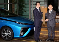 トヨタ自動車の燃料電池車「MIRAI」の前で、豊田章男社長(右)から鍵を引き渡される安倍晋三首相(当時)=首相官邸で2015年1月15日午後3時2分、森田剛史撮影