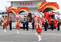 A corps of color guards performs with a band and popular character Mukku, in the background, during the Tokyo Fire Department's New Year drills in the capital's Koto Ward on Jan. 6, 2021. (Mainichi/Kota Yoshida)