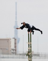 A performer puts on a display of traditional firefighting acrobatics on bamboo ladders during the Tokyo Fire Department's New Year drills in the capital's Koto Ward on Jan. 6, 2021. Tokyo Skytree is seen in the background. (Mainichi/Kota Yoshida)