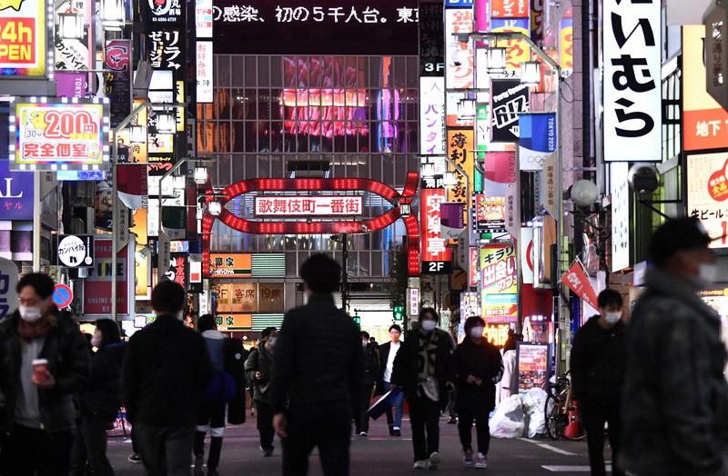 新型コロナウイルスに関するニュースが電光掲示板に流れる中、新宿・歌舞伎町を歩く人々=東京都新宿区で2021年1月6日、西夏生撮影