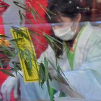 十日えびすで福笹を配る福娘。疫病退散と書かれた飾り=大阪市浪速区の今宮戎神社で2021年1月9日午後4時51分、平川義之撮影