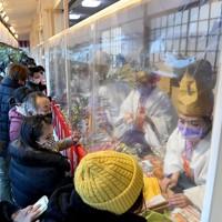マスクをして福ザサに縁起物を取り付ける福娘たち。参拝客との間にはビニールシートでついたてが立てられていた=大阪市浪速区で2021年1月9日午後4時半、平川義之撮影
