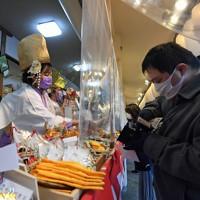 マスクをして福ザサに縁起物を取り付ける福娘たち。参拝客との間にはビニールシートでついたてが立てられていた=大阪市浪速区で2021年1月9日午後4時59分、平川義之撮影