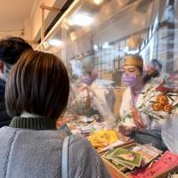マスクをして福ザサに縁起物を取り付ける福娘たち。参拝客との間にはビニールシートでついたてが立てられていた=大阪市浪速区で2021年1月9日午後4時33分、平川義之撮影