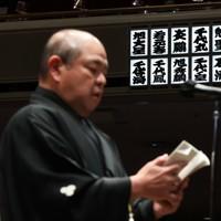 十両以上の休場力士16人の名前が並んだ掲示板。手前は、あいさつする日本相撲協会の八角理事長=東京・両国国技館で2021年1月10日、吉田航太撮影
