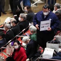 観客にマスク着用を呼びかける元琴陞菊の秀ノ山親方(中央右)=東京・両国国技館で2021年1月10日、玉城達郎撮影