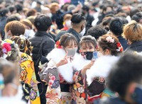 People celebrating their coming-of-age take a selfie in front of a ceremony venue in the Fukuoka Prefecture city of Kitakyushu, on Jan. 10, 2021. (Mainichi/Toyokazu Tsumura)