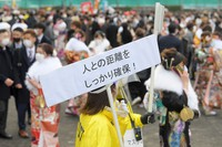A staffer at a coming-of-age ceremony in the Fukuoka Prefecture city of Kitakyushu is seen carrying a sign that reads,