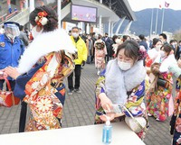 Those participating in a coming-of-age ceremony in the Fukuoka Prefecture city of Kitakyushu are seen disinfecting their hands before heading into the venue, on Jan. 10, 2021. (Mainichi/Toyokazu Tsumura)
