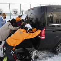 立ち往生した乗用車を押す消防隊員ら=福井市で2021年1月11日午後3時26分、山田尚弘撮影